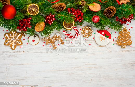 istock Christmas background with tree branches, ball toys, stars, gingerbread cookies 1044689744