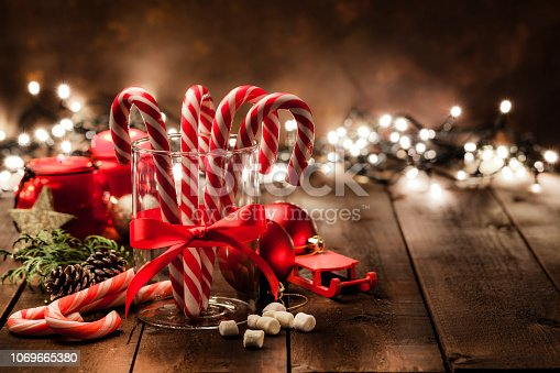 Front view of a glass cup with four candy canes inside shot on rustic wooden table. The cup has a red tied bow and is surrounded by some Christmas ornaments. Christmas lights are out of focus at background. The composition is at the left of an horizontal frame leaving useful copy space for text and/or logo. Predominant colors are red and brown. Low key DSRL studio photo taken with Canon EOS 5D Mk II and Canon EF 100mm f/2.8L Macro IS USM.