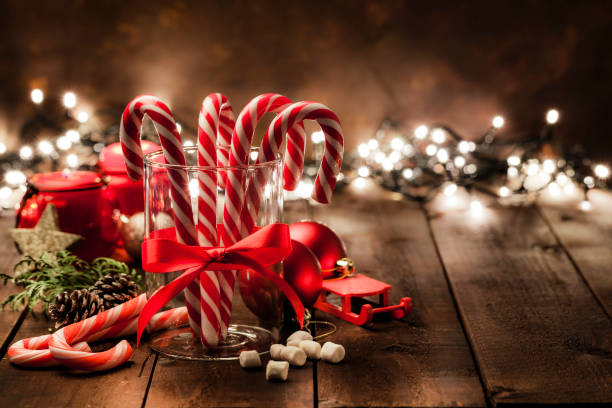 Christmas backgrounds: Candy canes in a glass cup on rustic wooden table Front view of a glass cup with four candy canes inside shot on rustic wooden table. The cup has a red tied bow and is surrounded by some Christmas ornaments. Christmas lights are out of focus at background. The composition is at the left of an horizontal frame leaving useful copy space for text and/or logo. Predominant colors are red and brown. Low key DSRL studio photo taken with Canon EOS 5D Mk II and Canon EF 100mm f/2.8L Macro IS USM. december stock pictures, royalty-free photos & images