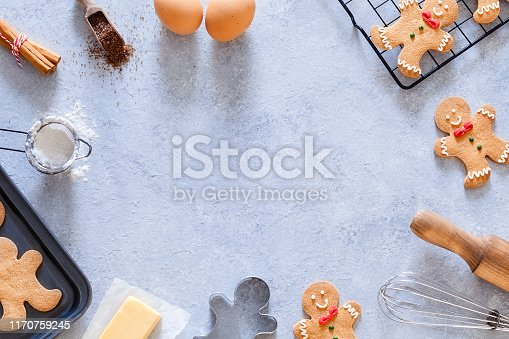 Top view of a gray table with ingredients and utensils for preparing Christmas cookies placed all around the borders making a frame and leaving useful copy space for text and/or logo at the center. Predominant colors are brown and gray. Low key DSRL studio photo taken with Canon EOS 5D Mk II and Canon EF 100mm f/2.8L Macro IS USM