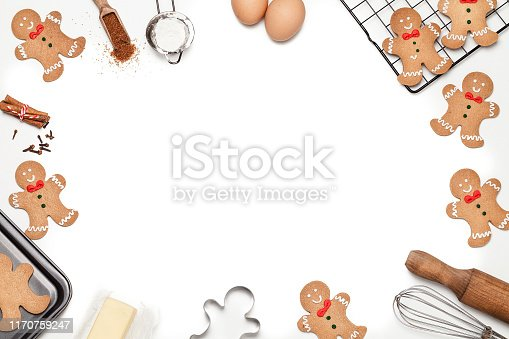 Top view of a white background with ingredients and utensils for preparing Christmas cookies placed all around the borders making a frame and leaving useful copy space for text and/or logo at the center. Predominant colors are brown and gray. Low key DSRL studio photo taken with Canon EOS 5D Mk II and Canon EF 100mm f/2.8L Macro IS USM