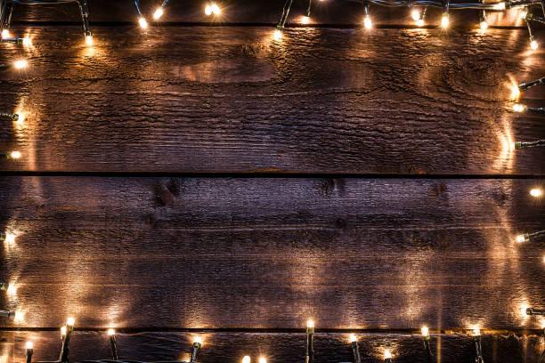 weihnachten hintergrund: leere rustikalen holztisch mit string leuchtet grenze - terrassen lichterketten stock-fotos und bilder