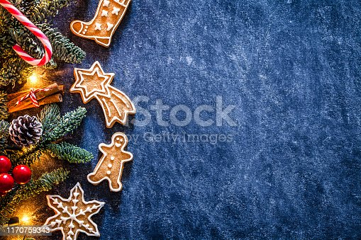 Top view of homemade gingerbread cookies and Christmas ornaments placed at the left of an horizontal abstract blue background making a frame and leaving a useful copy space for text and/or logo at the right. Predominant color are brown and blue. DSRL studio photo taken with Canon EOS 5D Mk II and Canon EF 100mm f/2.8L Macro IS USM