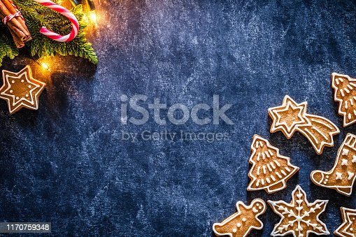 Top view of homemade gingerbread cookies and Christmas ornaments placed at the bottom right and top left corners of an horizontal abstract blue background making a frame and leaving a useful copy space for text and/or logo at the right. Predominant color are brown and blue. DSRL studio photo taken with Canon EOS 5D Mk II and Canon EF 100mm f/2.8L Macro IS USM