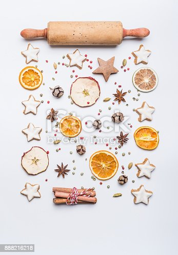 istock Christmas bake flat lay composition with rolling pin, star cookies , dried fruits and spices on white background, top view. 888216218