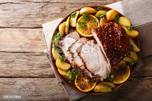 istock Christmas baked pork with potatoes, oranges and apples. horizontal top view from above 1057427834