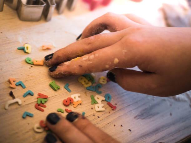 Weihnachtsbäckerei: kleines Mädchen sammeln essbare Briefe für Cookies – Foto