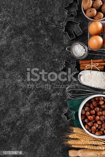 Christmas baking background with pastry cutters and cookie ingredients on dark kitchen table