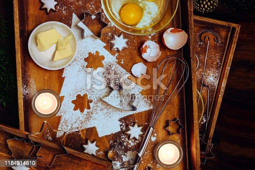 Christmas baking composition, fir tree shape from flour, butter, egg and cinnamon stars, utensils and candles on warm brown wooden trays, flat lay, high angle view from above