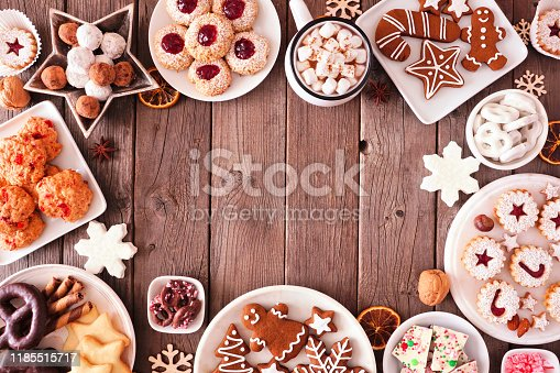 Christmas table scene of mixed sweets and cookies. Above view over a rustic wood background. Holiday baking concept.