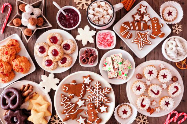 escena de la mesa de hornear de navidad con dulces variados y galletas, vista superior sobre un fondo de madera rústica - postre fotografías e imágenes de stock