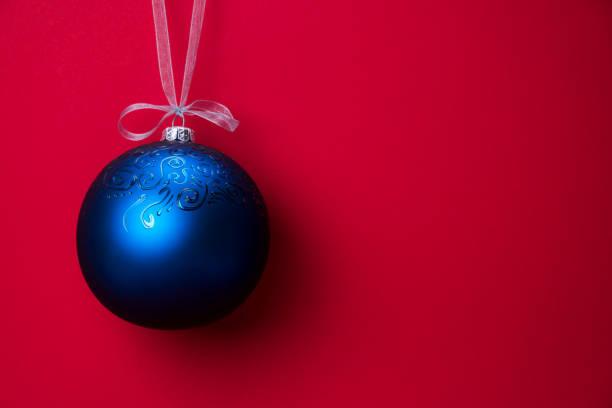 Weihnachtskugel hängt an einem Band über rotem Hintergrund. Kopieren Sie den Speicherplatz. – Foto