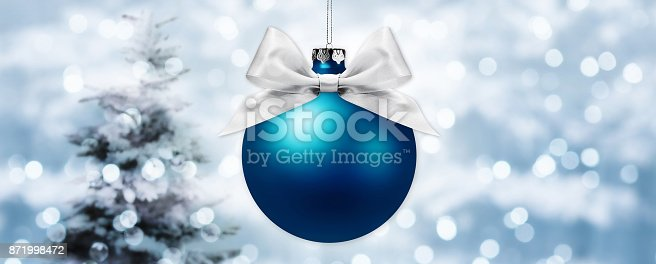istock christmas ball with silver ribbon bow on blurred lights background with tree 871998472