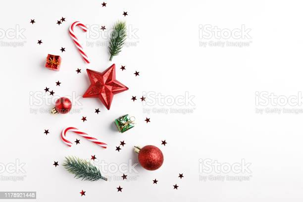Photo of Christmas balls, fir tree branches and Christmas ornament on white background.