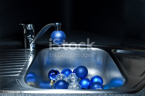 istock Christmas balls flowing from a faucet in the kitchen sink 1173586486