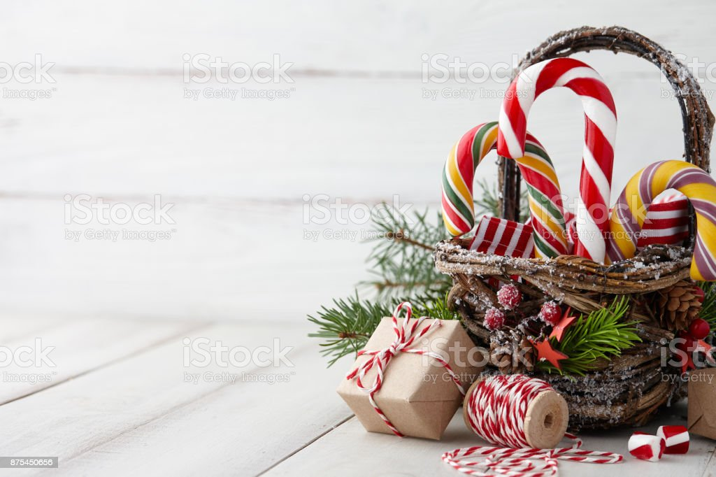 Christmas basket with candy canes on white planks royalty-free stock photo