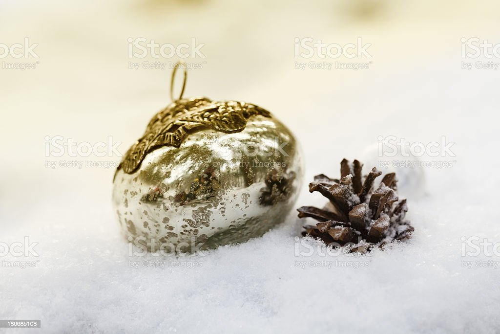 christmas bauble and pine cone outdoors in snow royalty-free stock photo