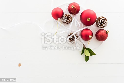 istock Christmas baubles and pine cones on background 867078992