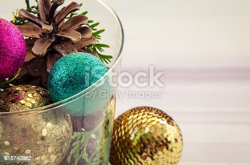 pine cone and colorful baubles in glass vase christmas concept