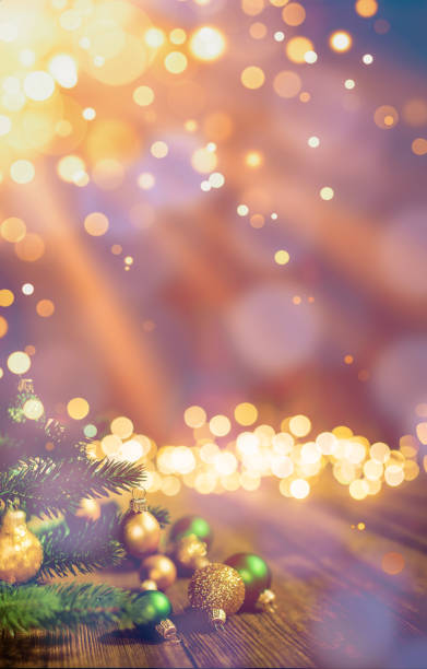 Christmas Baubles, sunlight beam lens flare on gold defocused sparkles stock photo