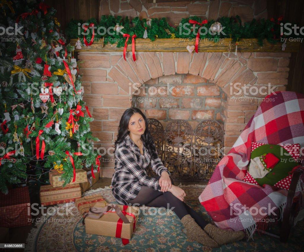 Christmas beautiful girl sitting near the fireplace stock photo