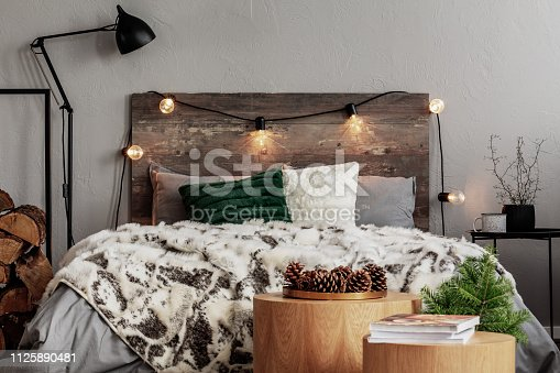 Christmas bedroom design with lights, spruce and cones