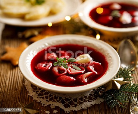 istock Christmas beetroot soup, borscht with small dumplings with mushroom filling in a ceramic bowl on a wooden table. 1055222474