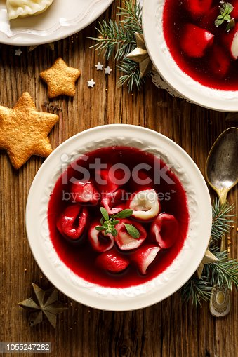 istock Christmas beetroot soup, borscht with small dumplings with mushroom filling in a ceramic bowl on a wooden table. 1055247262