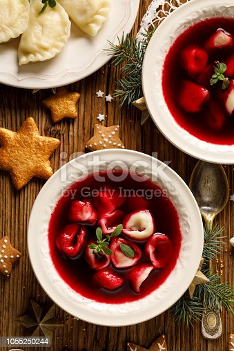 istock Christmas beetroot soup, borscht with small dumplings with mushroom filling in a ceramic bowl on a wooden table. 1055250244
