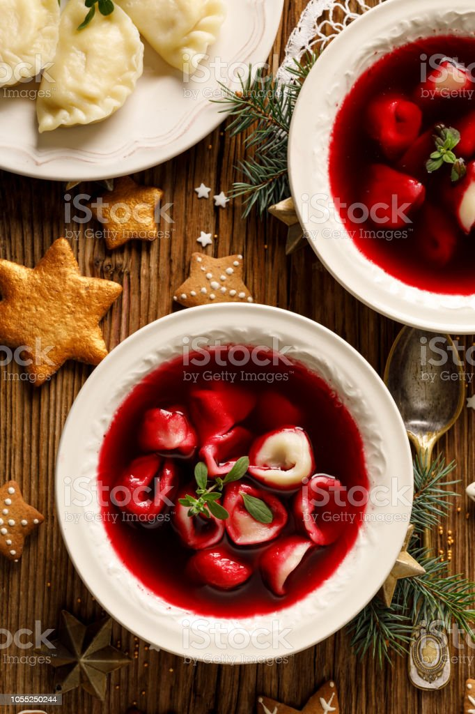 Christmas beetroot soup, borscht with small dumplings with mushroom filling in a ceramic bowl on a wooden table. stock photo