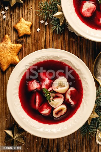 istock Christmas beetroot soup, borscht with small dumplings with mushroom filling in a ceramic bowl on a wooden table. 1060527264