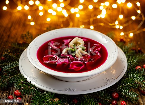 istock Christmas beetroot soup, red borscht with small dumplings with mushroom filling in a ceramic white plate on a wooden table 1180618961