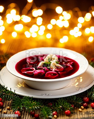 istock Christmas beetroot soup, red borscht with small dumplings with mushroom filling in a ceramic white plate on a wooden table close-up. 1180958259