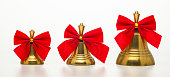 Christmas bells with red bows isolated on white background