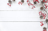 Christmas berry garland and pine cone border on an old white wood background