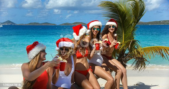 Christmas bikini girls with drinks on a palm tree at a tropical beach in the Caribbean