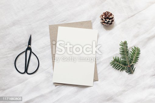 istock Christmas blank greeting card mock-up scene. Festive winter wedding composition. Envelope, pine cone, black vintage scissors and fir tree branch on white table, linen background. Flat lay, top view. 1171660805