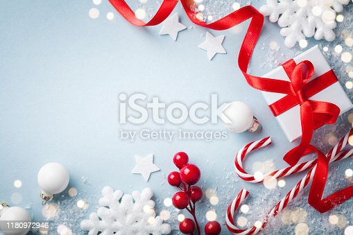 1076063742 istock photo Christmas blue background. Gift or present box and holiday decorations top view. Happy New Year greeting card. 1180972946