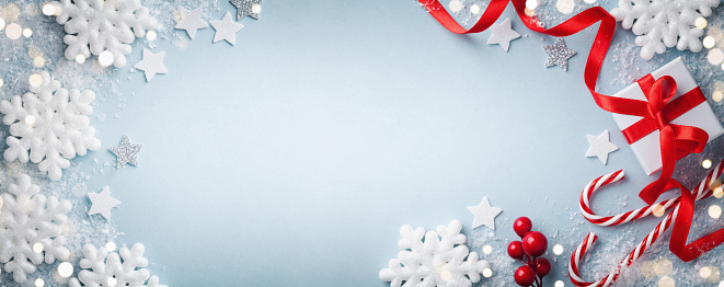 Christmas blue background. Gift or present box, white snowflakes and holiday decoration top view. Happy New Year greeting card. Banner format.