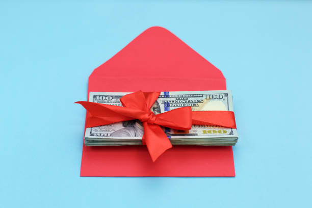 Christmas Bonus Stack of Cash With Red Bow on the red envelope Isolated on blue Background. stock photo