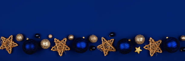 Christmas border banner of dark blue and gold ornaments ,top view on a midnight blue background stock photo