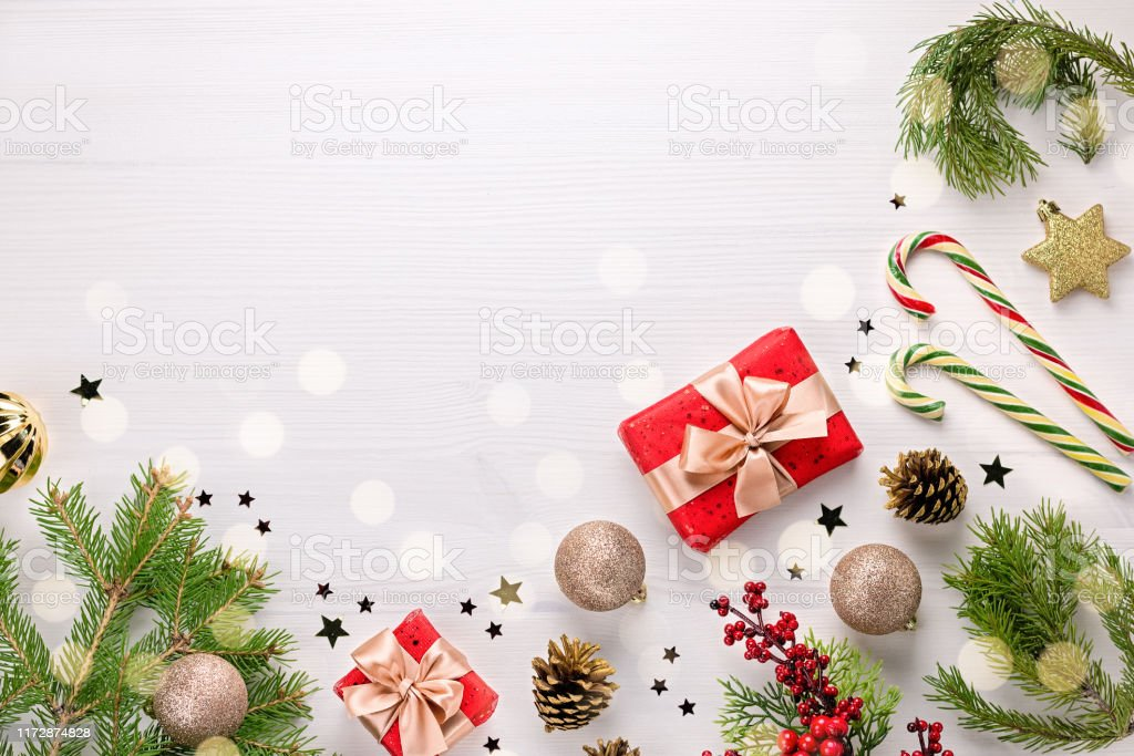 Christmas card with fir tree branches, golden decorations, sweets and...