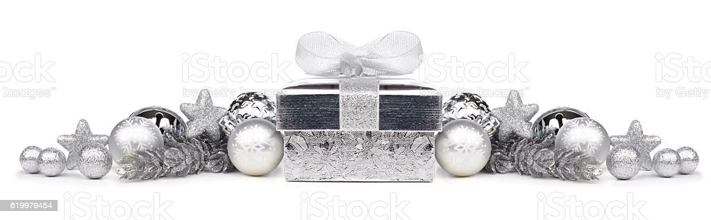 Christmas border of silver ornaments and gift over white stock photo