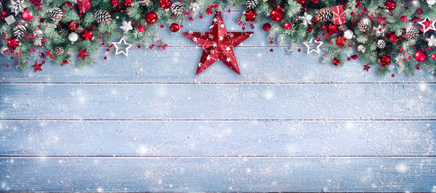 christmas border - pine branches and red star on wooden - garland stock photos and pictures