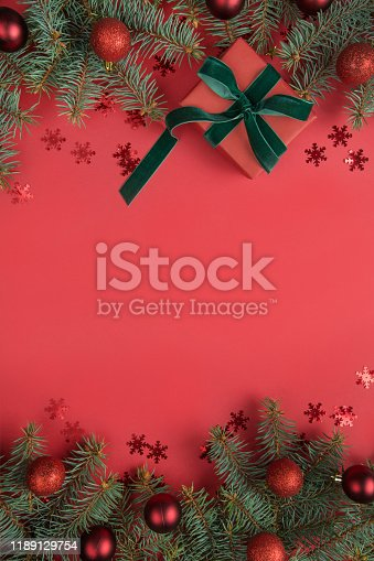 1062680370 istock photo Christmas border with fir tree and gift on red background. Greeting card. Winter holiday. Happy New Year. Space for text. Top view. Flat lay. 1189129754