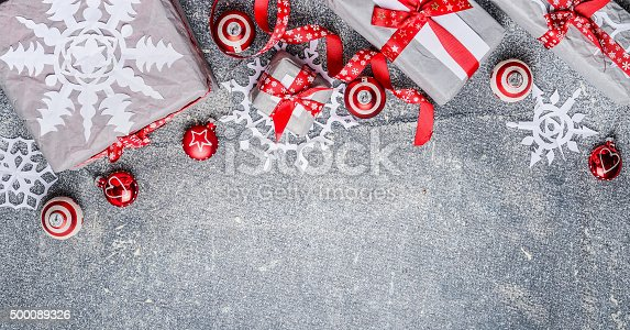 istock Christmas border with gift boxes, paper snowflakes, red ribbons 500089326