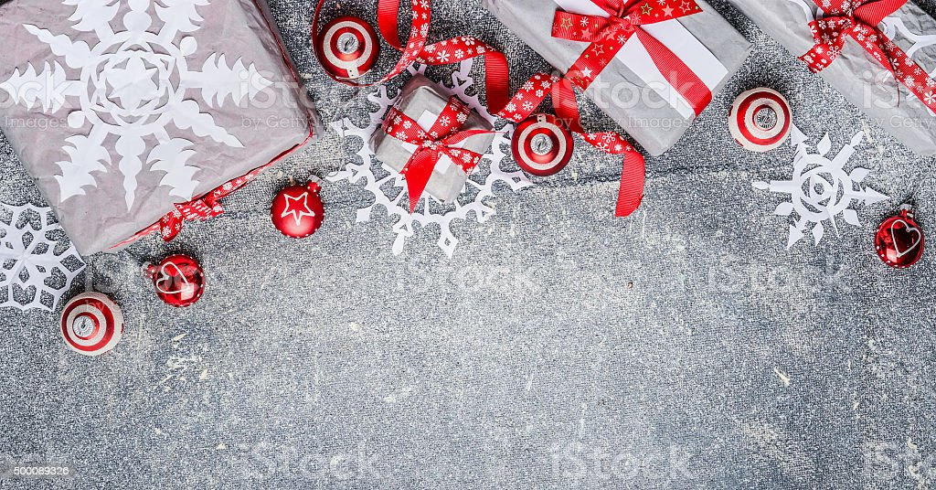 Christmas border with gift boxes, paper snowflakes, red ribbons stock photo