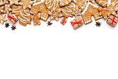 Christmas border with gingerbread cookies and aromatic spices on white background, copy space, top view
