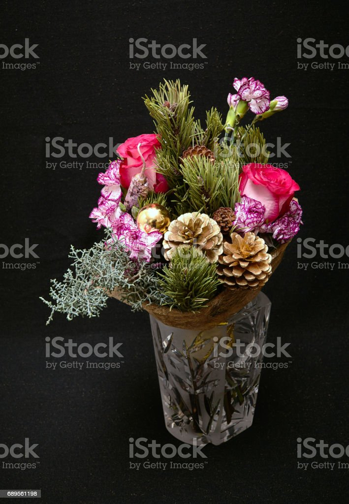 Christmas bouquet with red roses, bush carnations, pine cones, cypress branches, pink pepper and yellow balls. New Year composition on a dark background. stock photo
