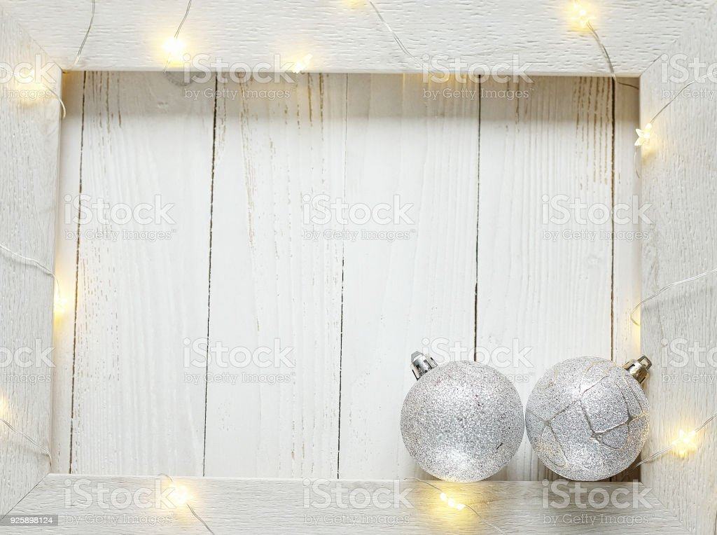 New year background of bright garlands on a wooden light background